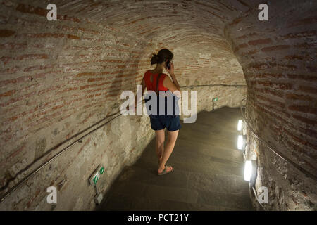 A tourist walking down the steps inside the White Tower of Thessaloniki and listening to the museum tour - Stock Image