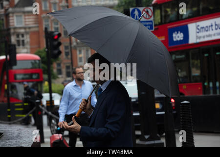London, UK. 18th June 2019.  London rain: a large umbrella will do nicely in the rain. Tourists and Londoners protecting themselves against the continuous rain in central London today. The Union Jack umbrella appears to be very popular. Credit: JoeKuis / Alamy - Stock Image