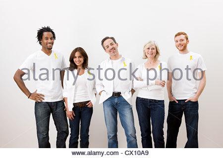 People wearing yellow awareness ribbons - Stock Image