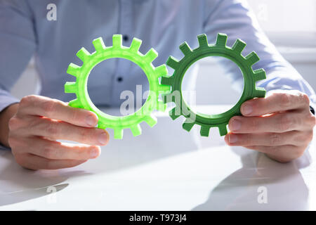 Businessman Joining Together Gears On Wooden Table At Workplace - Stock Image