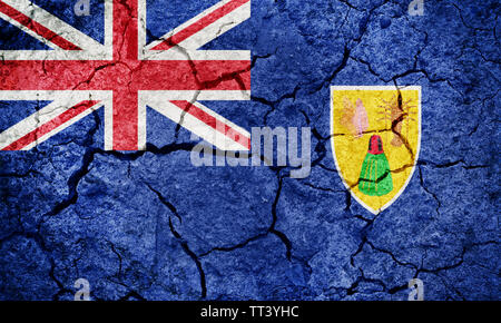 Turks and Caicos Islands flag on dry earth ground texture background - Stock Image