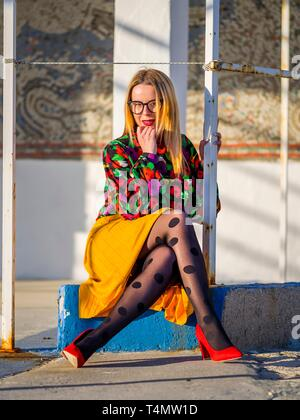 Young woman legs heels enjoying sun looking at camera - Stock Image