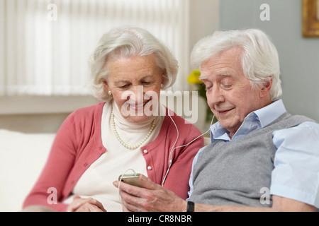 Senior couple listening to mp3 player - Stock Image