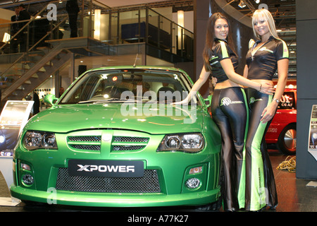 Two models pose with an MG Xpower car on the MG Rover stand at the UK Motorshow NEC Birmingham May 2004 - Stock Image