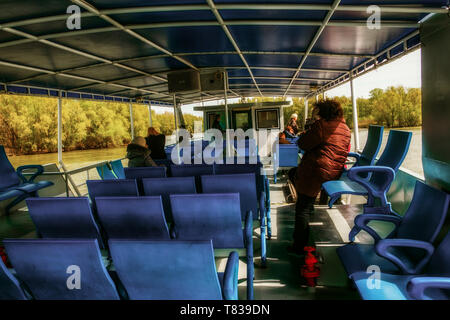 Nature Reserve Delta of the Danube River. Romania. April 20, 2019. A cruise ship swims along the river. Tourists on deck look around. - Stock Image
