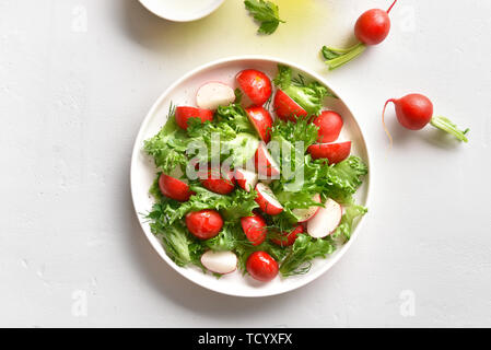 Vegetable salad from radish and lettuce leaves on plate over white stone background. Top view, flat lay - Stock Image