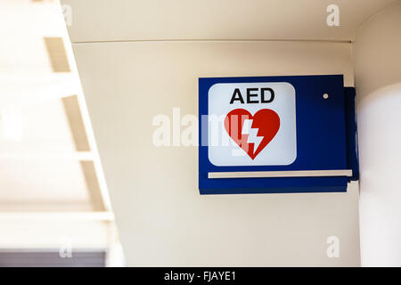 Automated External Defibrillator AED sign mounted to a wall at an airport. - Stock Image