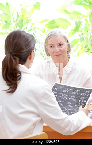Female doctor with an mra image or angiogram discussing with a senior patient her risk to suffer an apoplectic stroke, copy space - Stock Image