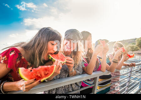 Cheerful group of people females friends having fun together in summer outdoor leisure activity eating fresh and diet red watermelon with laughs - You - Stock Image