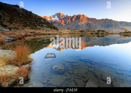 Rocky peaks of Mount Disgrazia reflected in Lake Zana at sunrise, Malenco Valley, Valtellina, Lombardy, Italy, Europe - Stock Image
