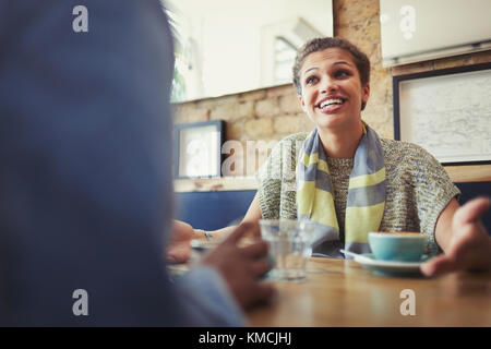 Smiling young woman talking to friend, drinking coffee at cafe table - Stock Image