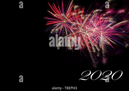 Bursting fireworks against black background celebrating the arrival of 2020, the end of a decade - Stock Image