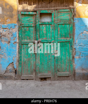 Closed green wooden grunge weathered abandoned door on dirty wall painted in yellow and blue colors - Stock Image