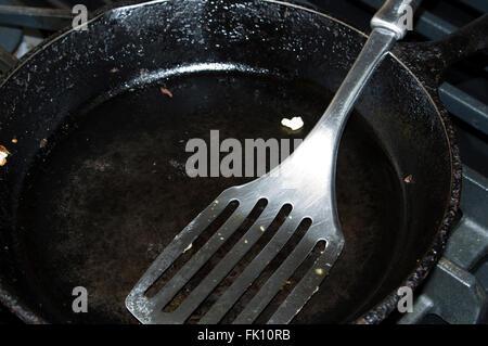 cast iron frying pan, spatula - Stock Image