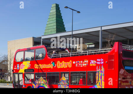 The City Sightseeing Oxford open-topped tour bus passes the Said Business School, Oxford - Stock Image