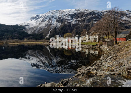 Reflection of a little village on the shores of lake Granvinsvatnet flanked by a mountain topped with a little snow. - Stock Image