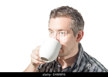 Picture of a man that is drinking coffee from a white cup - Stock Image
