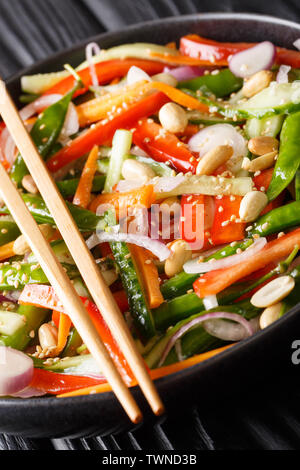 Vegetarian vegetable salad with sesame and peanuts close-up on a plate on the table. vertical - Stock Image
