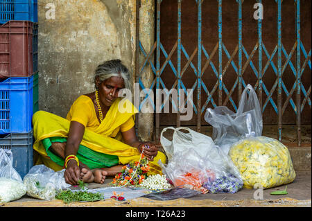 Preparing and selling flowers in a flower market in George Town, Chennai - Stock Image