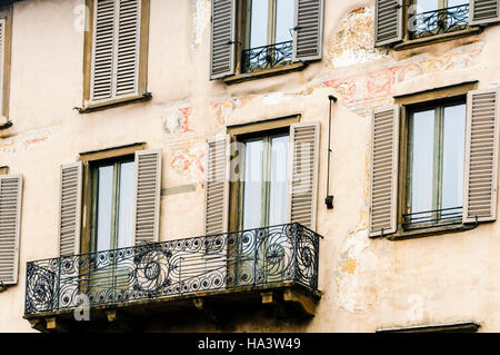 Buildings with shuttered windows and traditional Italian wrought iron balcony in Citta Alta, Bergamo, Italy - Stock Image