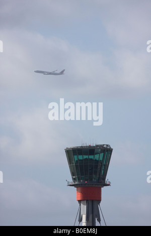 Air control tower and passenger airplane flying out of London Heathrow in the background. - Stock Image