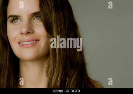Young woman looking away and smiling, portrait - Stock Image