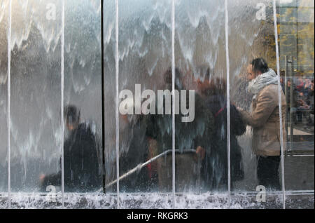 customers behind the glass fountain entering Apple store in Milan, Italy - Stock Image