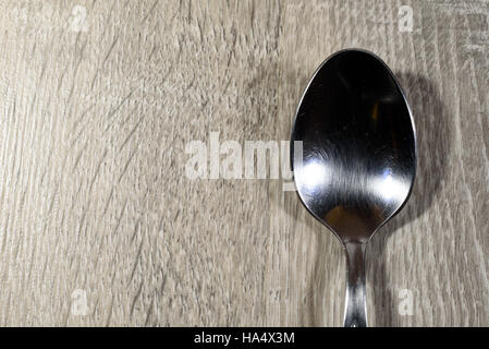 Single shiny empty silver spoon on a wooden kitchen background - Stock Image