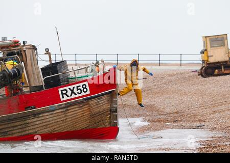 Hastings, East Sussex, UK. 05 Jan, 2019. UK Weather: A fisherman jumps from his fishing boat after landing at shore onto the stade, the largest beach launched fishing fleet in the UK, Hastings, East Sussex. © Paul Lawrenson 2018, Photo Credit: Paul Lawrenson / Alamy Live News - Stock Image