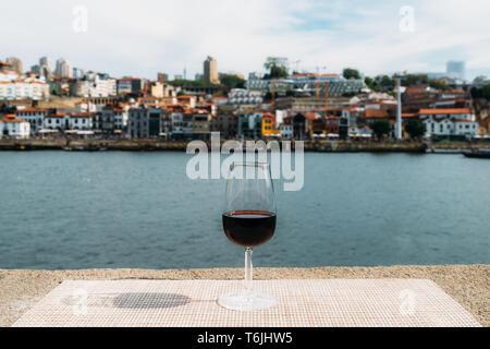 Selective focus of small glass of red Port wine overlooking Vila Nova de Gaia embankment at Cais da Ribeira on the River Douro in Porto, Portugal - Stock Image