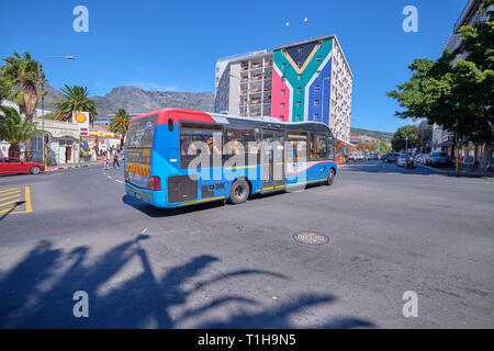 Myciti bus turning on Street in centre with Table Mountain in background, and apartment building in color of Flag. Cape Town, South Africa, - Stock Image