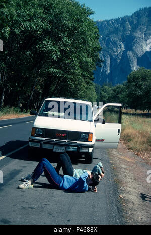 Two tourists lie on their back son the roadside to look up at El Capitan, Yosemite, California - Stock Image