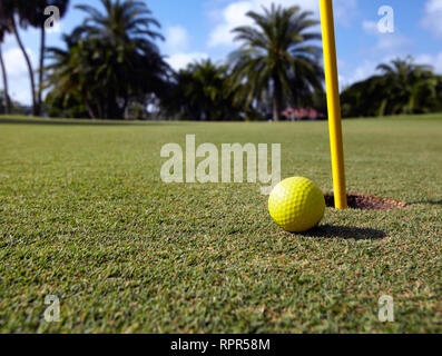 Golf Ball Lying Next to the Hole - Stock Image