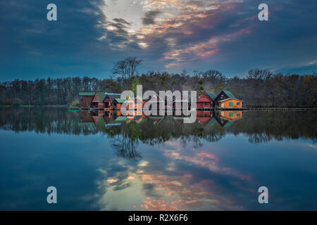 Tata, Hungary - Beautiful sunset over wooden fishing cottages on a small island at lake Derito (Derito to) in November with reflection - Stock Image