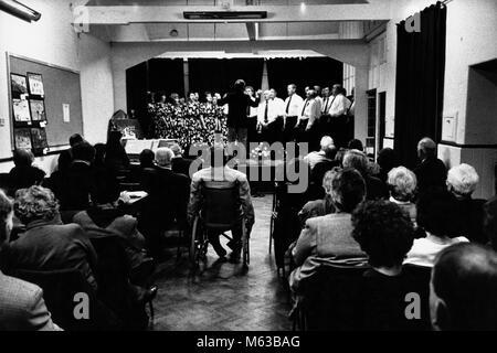 Choir singing on stage at small eisteddfod in village hall Talsarnau Gwynedd Wales UK - Stock Image