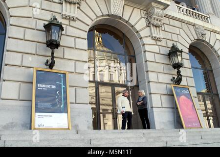 Two people chat in front of a window in San Francisco, near City Hall. - Stock Image