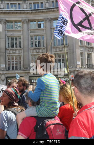 London, UK. 19th Apr, 2019. A child seen on the shoulders of their parent among protesters during the demonstration.Environmental activists from Extinction Rebellion movement occupy London's Oxford Circus for a 5th day. Activists parked a pink boat in the middle of the busy Oxford Circus road junction blocking the streets and causing traffic chaos. Credit: Keith Mayhew/SOPA Images/ZUMA Wire/Alamy Live News - Stock Image