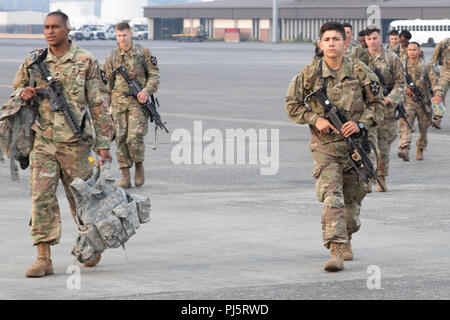 """Soldiers from the 1-2 Stryker Brigade Combat Team, walk toward a charter aircraft Aug. 25, 2018, at Joint Base Lewis-McChord, Washington. These Soldiers had received notice to deploy to the National Training Center at Fort Irwin, California. In response, a battalion-sized element known as """"Task Force Regulars"""" conducted an Emergency Deployment Readiness Exercise and sent Soldiers by air through McChord Field to NTC. - Stock Image"""