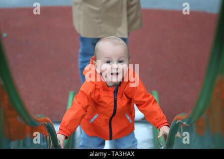 Smiling Baby Boy With Orange Raincoat Climbing Up The Slide - Stock Image