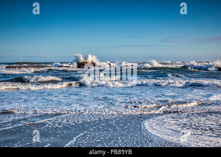 Waves rushing at the shore and splashing over rocks just before high tide. - Stock Image