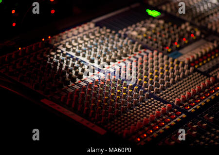 Mixing board with knows and green LED lights in a dark venue with narrow depth of field - Stock Image