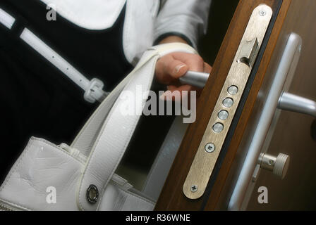 A woman entering a room holding a door handle - Stock Image