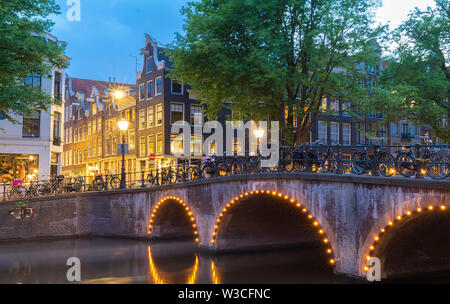 Night city view of Amsterdam canal, typical dutch houses , Holland, Netherlands. - Stock Image