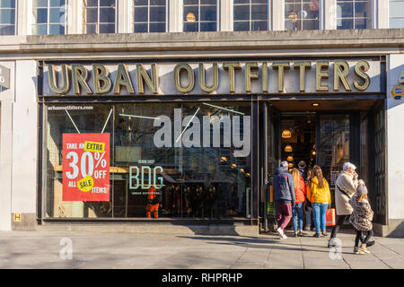 Shoppers enter an Urban Outfitters store front facade in Above Bar Southampton precinct, England, UK - Stock Image