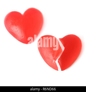 Broken heart or heartache concept with two bright red jelly heart shaped sweets next to each other with one cut in half isolated on white background - Stock Image