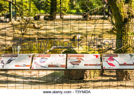 Poznan, Poland - April 18, 2019: Information boards with birds descriptions in front of a cage in the old zoo. - Stock Image