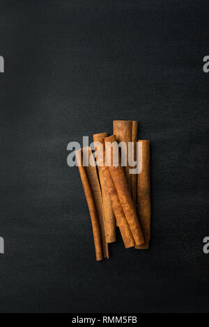 Bunch of cinnamon sticks on blackboard background with chalk smudges texture. Vintage rustic style. Holiday baking beverages ingredient. Healthy spice - Stock Image