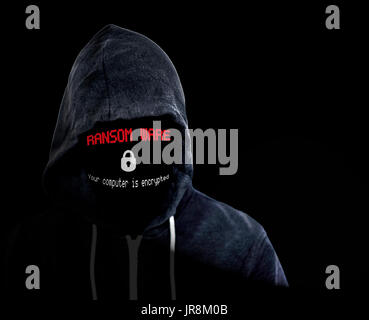 Hooded unknown anonymous criminal with a computer ransomeware threat in place of his faceless face - Stock Image
