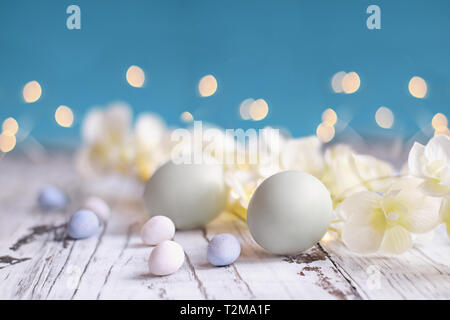Natural colored Easter eggs, malt candy covered chocolate eggs, and flower blossoms over a rustic white wood table against a blue background. - Stock Image