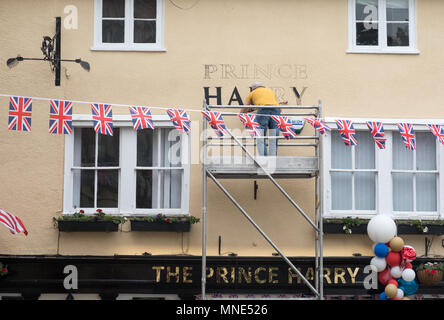 Royal Wedding preparations in Windsor town centre. A signwriter paints 'Prince Harry' on a pub which has changed its name from 'The Three Tuns' to 'The Prince Harry' - Stock Image